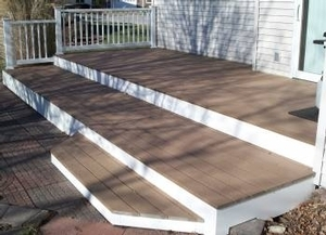 This is a simple 2-level composite deck with white trim & white railing system.