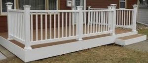 We customized this front entry deck with solid composite decking boards, white railing with solar powered lights on corner post and white trim boards.