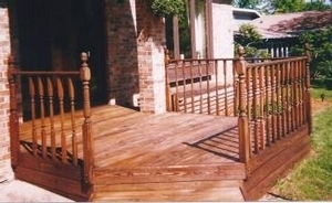 A nice small wood entry deck with a wood handrail & more ornate spindles.